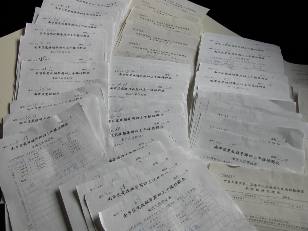 The many petition forms a resident, who lost her home to domicide in 1996, filled out at a petition office in Shanghai and brought back home because the office refused to receive her (Photographed by Qin Shao, 2004)