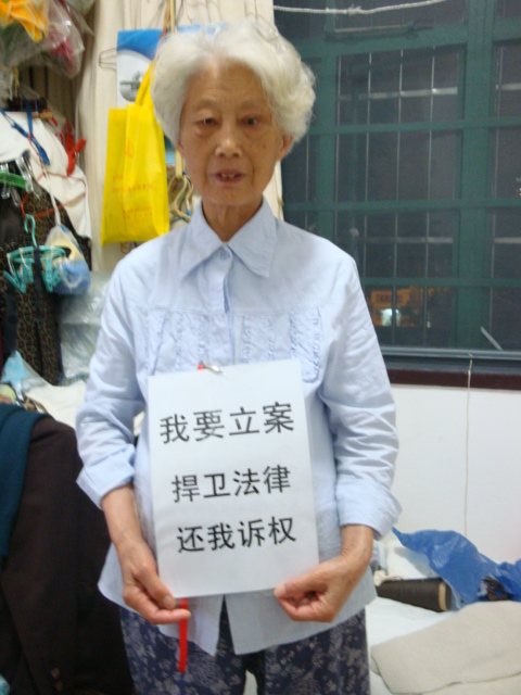 """Mrs He (under house arrest, her home was demolished for the China National Pavilion) holding a statement that reads """"I want my complaint to be lodged by the courtroom. Please defend the law and respect my right to sue."""""""