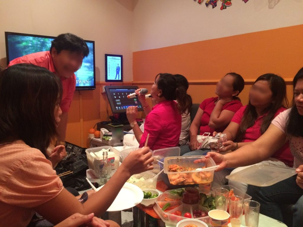 A group of domestic workers celebrate one of their birthdays at a karaoke bar. They bought food, drink and a cake to celebrate (photo author's own, 2017).