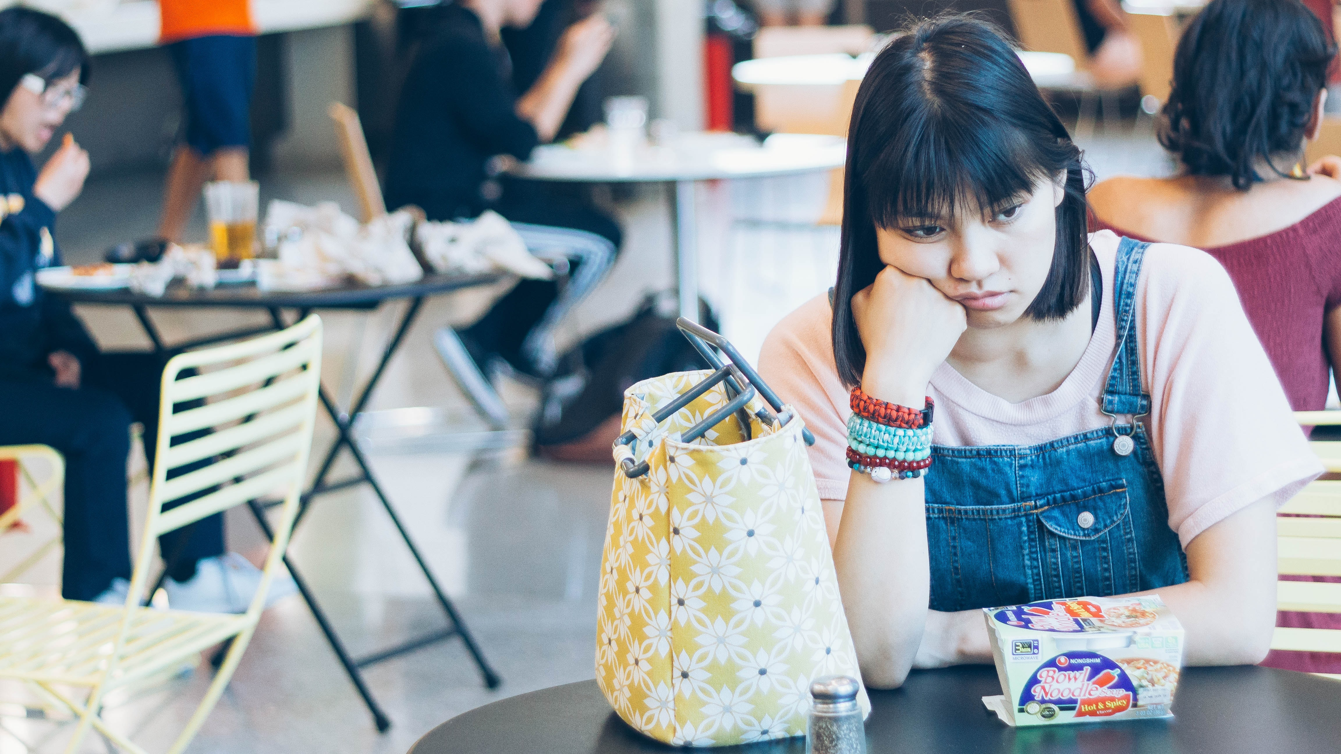 female student looking fed up at sitting at table