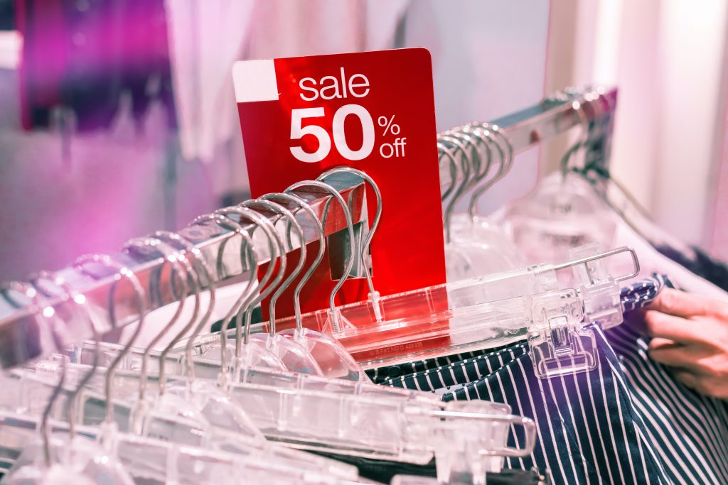 A rail of clothes in a shop with a sale tag.