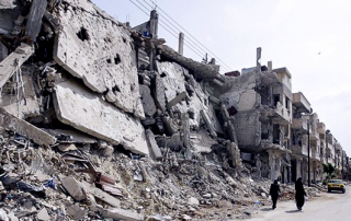 Syrian_women_walk_past_destruction_in_the_Bab_Amro_neighbourhood_of_Homs_on_May_2,_2012.