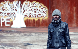 A refugee stands in front of a graffiti painting of a tree next to the word 'hope'