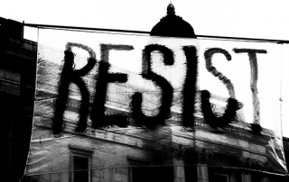 Black and white photo of a banner at a protest which reads, 'resist'.