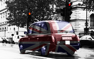 An artistic graphic of a London taxi decorated with the Union Jack Flag with a number plate that says 'BREXIT' waiting at a red traffic light