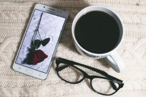 A phone, a pair of glasses and a cup of coffee.