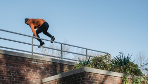 Person jumping over metal railing